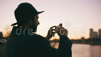 Silueta del hombre del viajero en el sombrero que toma la foto panorámica del horizonte de la ciudad en su cámara del smartphone  metrajes