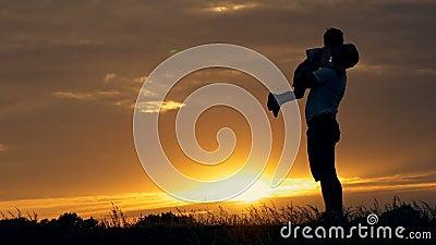 Silueta del padre feliz de la familia de la madre y de dos hijos que juegan al aire libre en campo en la puesta del sol almacen de video