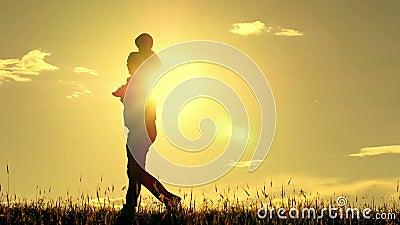Silueta del padre y del hijo que caminan en fondo de la puesta del sol El papá está deteniendo a su hijo en sus hombros El concep metrajes