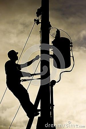 Siluetta del lavoratore ad una linea elettrica posta