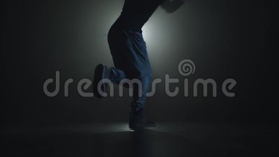 Siluetta del primo piano di giovane ballerino di talento che balla ballo hip-hop della via su una fase davanti al riflettore archivi video