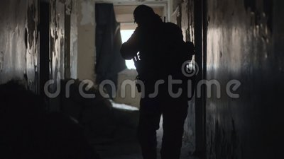 Siluetta del soldato con la camminata dell'arma in costruzione durante l'operazione militare stock footage