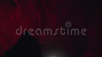 Siluetta dell'uomo con un segnale rosso che brucia le pietre nel buio della grotta, concetto di turismo estremo archivi video