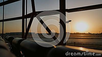 Siluetta di un aeroplano che decolla al tramonto all'aeroporto di Pechino nei precedenti di una finestra archivi video