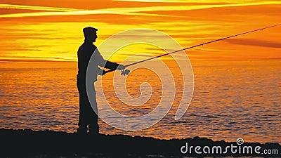 Siluetta di un pescatore con una canna da pesca al tramonto sopra il mare archivi video