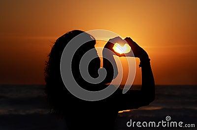 Siluetta di una donna con le sue mani che formano un cuore, al