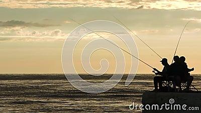 Siluette dei pescatori all'alba sul bacino video d archivio