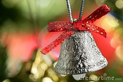 Silver bell in the christmas tree with red ribbon