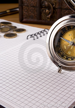 Silver compass, coin and notebook