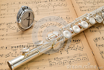 Silver flute and pocket metronome on an ancient music score Stock Photo