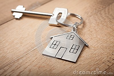 Close up silver home shaped keychain with key on wooden background. Mortgage, investment, real estate, property and new home conce Stock Photo