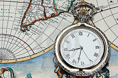 Silver pocket watch over old world map