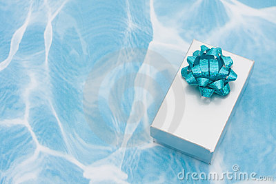 A silver present with bow on aqua background