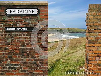 Sinal do paraíso na parede de tijolo velha, praia do mar/oceano