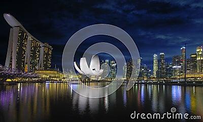 Singapur-Skyline durch Fluss-Ufergegend an der Dämmerung