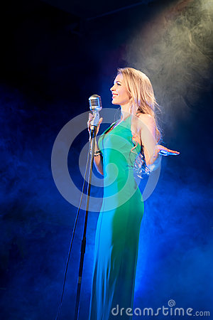 Free Singer Woman Singer Sings A Song With Retro Microphone On Blue Smoke Background. Concert Stock Images - 86241094
