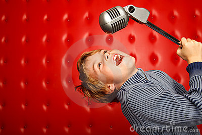 Singing boy with microphone on rack against wall