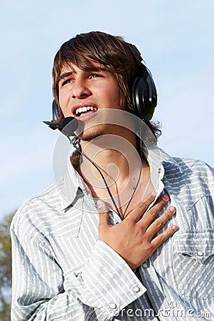 Singing teenage boy in headphones