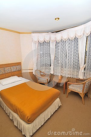 Single bed in hotel room with furniture