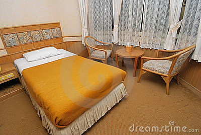 Single bed in modern hotel room with chairs