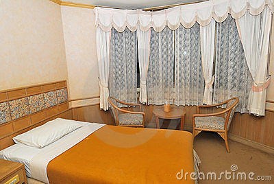 Single bed in modern hotel room with furniture