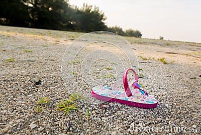 Single child flipflop on empty beach