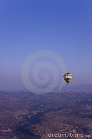 Single hot air balloon flying in mountains