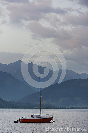 Single sail boat swims on lake