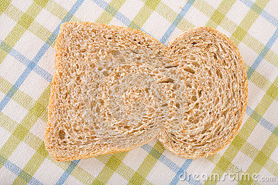 Single slice of wholemeal bread on linen cloth