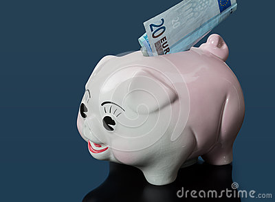 20 euro bill in slot of piggy bank