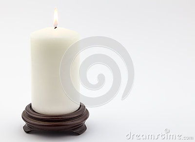 single white lit candle on white background stock photo