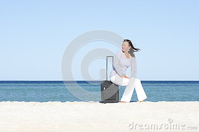 Single woman waiting with luggage at seaside