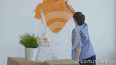 Singleton Lifestyle- und Renovierungskonzept Flachrenovierungskonzept Happy Maler mittleren Alters mit weißer Wand stock footage