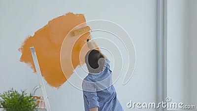 Singleton Lifestyle- und Renovierungskonzept Flachrenovierungskonzept Happy Maler mittleren Alters mit weißer Wand stock video footage
