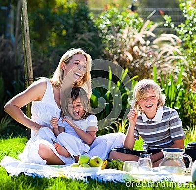 Sira de mãe e suas crianças que jogam em um piquenique