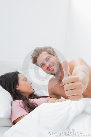 Sirva el donante del pulgar para arriba al lado de su socio durmiente