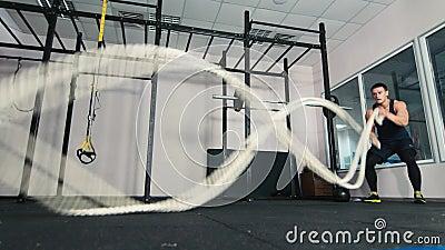 Sirva hacer ejercicio de lucha de la cuerda en el gimnasio metrajes