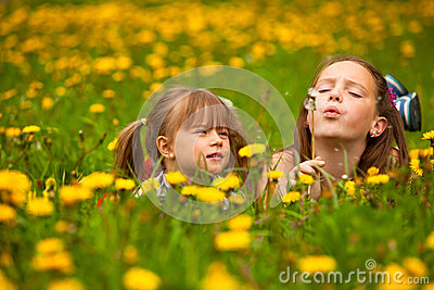 Sister blowing dandelion seeds away