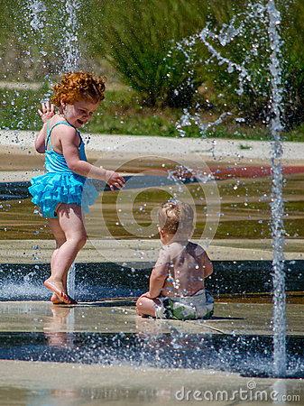 Sister and brother in a city fountain Editorial Stock Photo