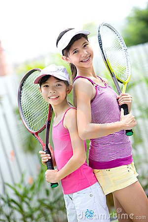 sisters back to back with a tennis racket each