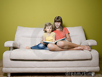 Sisters with book on sofa