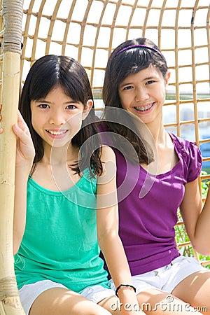Sisters enjoying the rattan swing