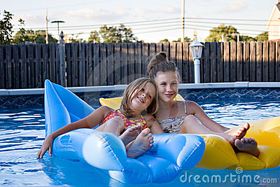 Sisters floating in the pool