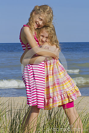 Sisters hugging at beach.