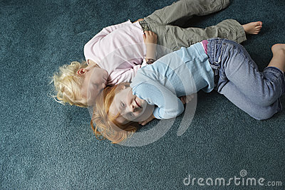 Sisters Lying On Carpet At Home