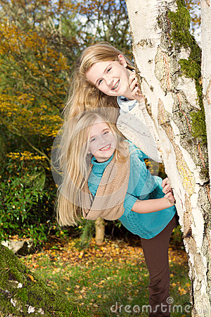 Sisters playing in the park during a nice autumn day