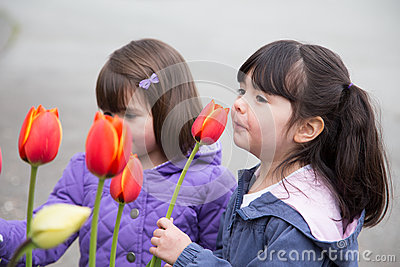 Sisters stopping to smell spring tulips