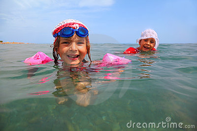 Sisters are swimming in sea. one girl in glasses