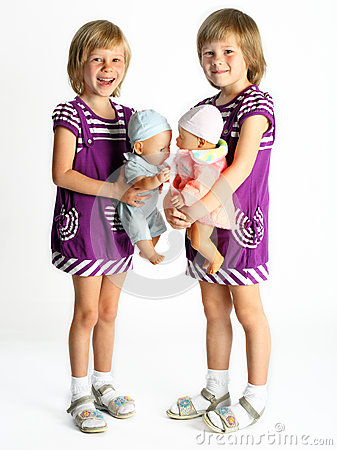 Sisters twins with dolls