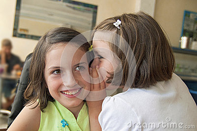 Sisters whispering on the ear